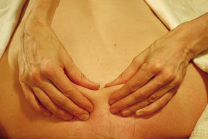 View of hands practicing rhythmical massage therapy at the base of patient's neck, between shoulder blades